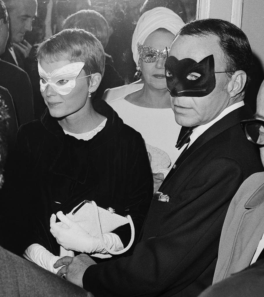 Frank Sinatra and his wife, actress Mia Farrow, arrive for a masked ball thrown by best-selling author Truman Capote.
